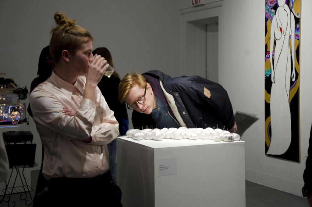 College seniors MJ Robinson and James Scott take a close look at a sculptural work by fellow College senior and artist Julia Harris at the annual Half-Time Show. The event featured student works produced during the first semester of the Art departments Senior Studio capstone program.
