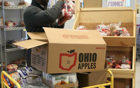 Food Distribution Coordinator Alan Mitchell at Oberlin Community Services stocks produce and nonperishable items as he prepares to serve food-insecure Ohioans.