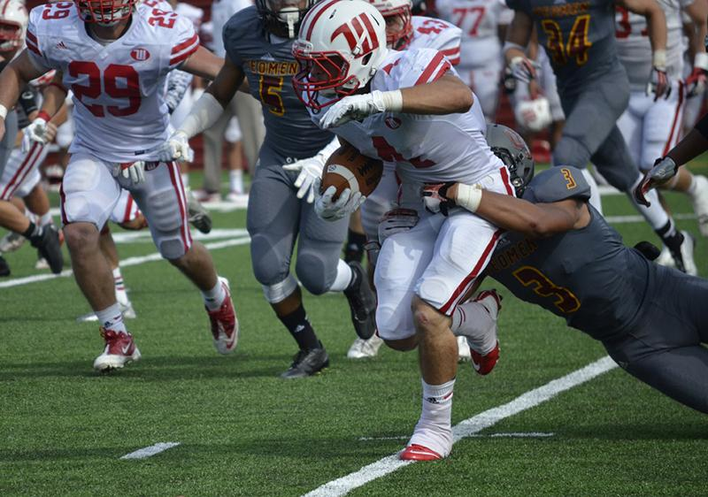 Sophomore defensive back Adrian Kelly drags down a Wittenberg University ball carrier in a game last Saturday. Kelly had 11 total tackles and a pass breakup in the game.