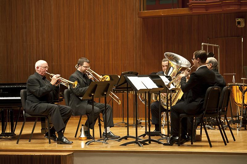 """A brass quintet performs Lutosławski's """"Mini Overture"""" in Warner Concert Hall. Associate Professor of Trumpet Roy Poper (left), Assistant Professor of Trombone Lee Allen, Visiting Professor of Tuba Denis Nulty, Professor of Horn Roland Pandolfi and Trumpet major and Conservatory senior Luke Spence played with precision and poise during this installment of the Faculty Chamber Series."""