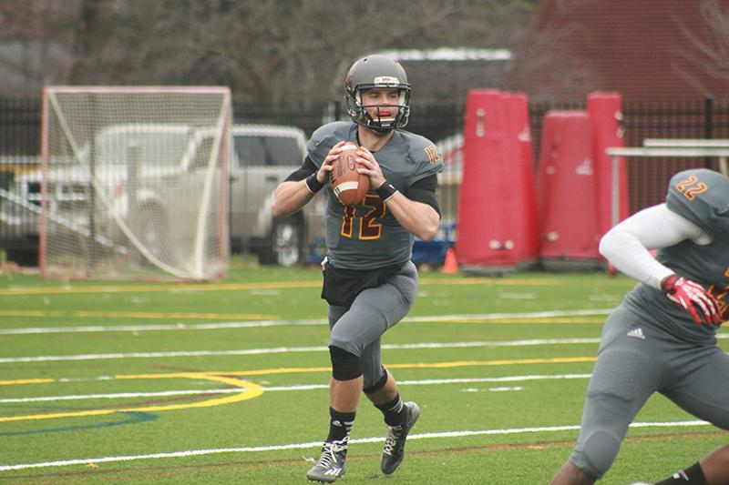 Junior quarterback Lucas Poggiali looks downfield in a game against the Ohio Wesleyan University Battling Bishops on Nov. 8. The football team concluded its season last weekend with a loss against the Hiram College Terriers, finishing with an overall record of 2–8.