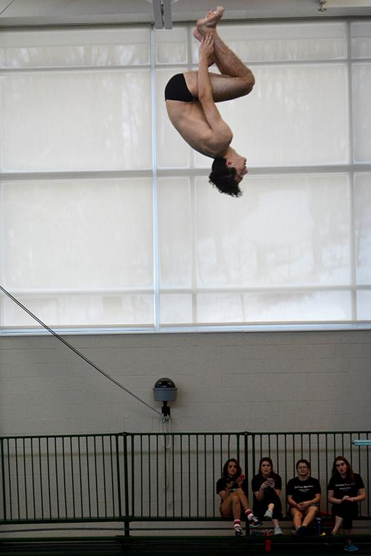 Sophomore Jean-Paul Gilbert flips in the men's diving competition at the North Coast Athletic Conference championships last weekend. The swimming and diving team concluded its regular season at the meet.