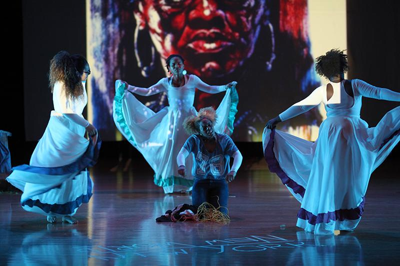 """College sophomore Cassie Brown (left), Tiachelle Clifford (center back) and College senior Gifty Dominah (right) shimmer under blue lights as they en- circle College senior Kara Mahon during her senior dance show. Mahon's show, titled """"Crossing Rivers: The Love of Afrikete,"""" combined traditional African movement with contemporary choreography to express deeply personal themes."""