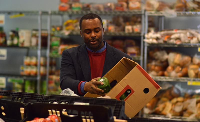 Alan Mitchell, food distribution coordinator of Oberlin Community Services, moves green peppers from the stock room to the food pantry. The organization has expanded significantly in the last year, both in the range of programs it operates and the number of people it serves.