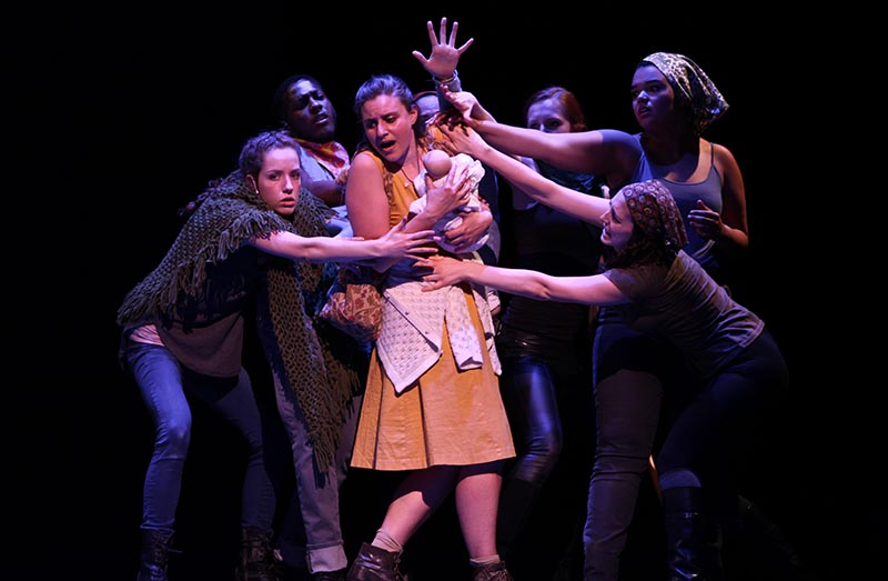 A cluster of actors gather around College senior Julia Melfi in The Caucasian Chalk Circle. The Oberlin Theater department premiered the famous play by German playwright Bertolt Brecht Thursday night.
