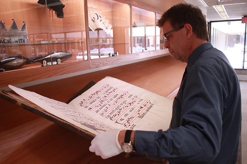 Special Collections and Preservation Librarian Ed Vermue opens a 15th century Northern-Italian antiphonal manu- script. Aside from his curatorial roles in the library, Vermue also operates the Oberlin Letterpress, where he runs special Winter Term and ExCo programs focused on book arts.