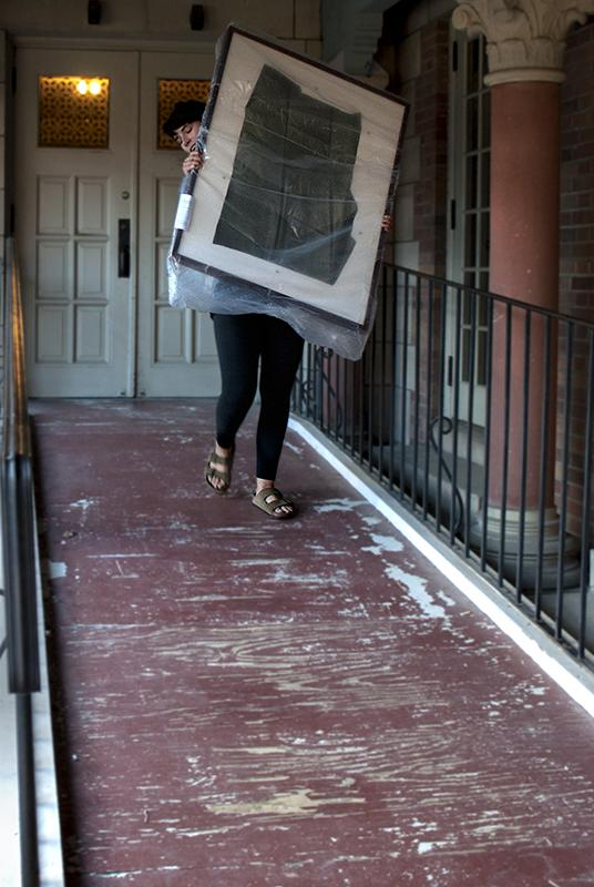 A student carries a piece of artwork out of the Allen Memorial Art Museum Saturday morning at the conclusion of Art Rental. Inclement weather and a new organization system resulted in a less chaotic event than in previous years.