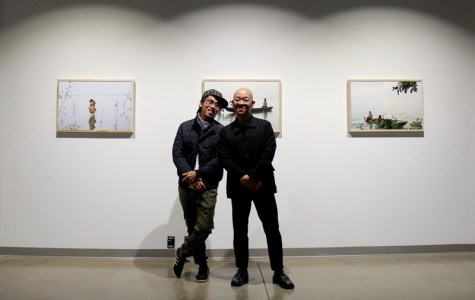 Oberlin's Artist in Residence for February, Duy Phuong Le Nguyen (left) and Art Department Co-chair Pipo Nguyen-Duy pose in front of Nguyen's photos in the Richard D. Baron '64 Art Gallery. The exhibit, Holding Water, depicts Tri An Lake in Vietnam.