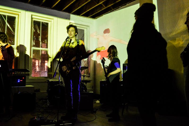 Julia Julian singer and guitarist Max Ripps (left) and bassist Cena Loffredo, both College first-years, interact with the audience between songs. Two other bands, Shya and Woof, joined Julia Julian for a night full of unorthodox indie rock by Oberlin student musicians at Storage Saturday.