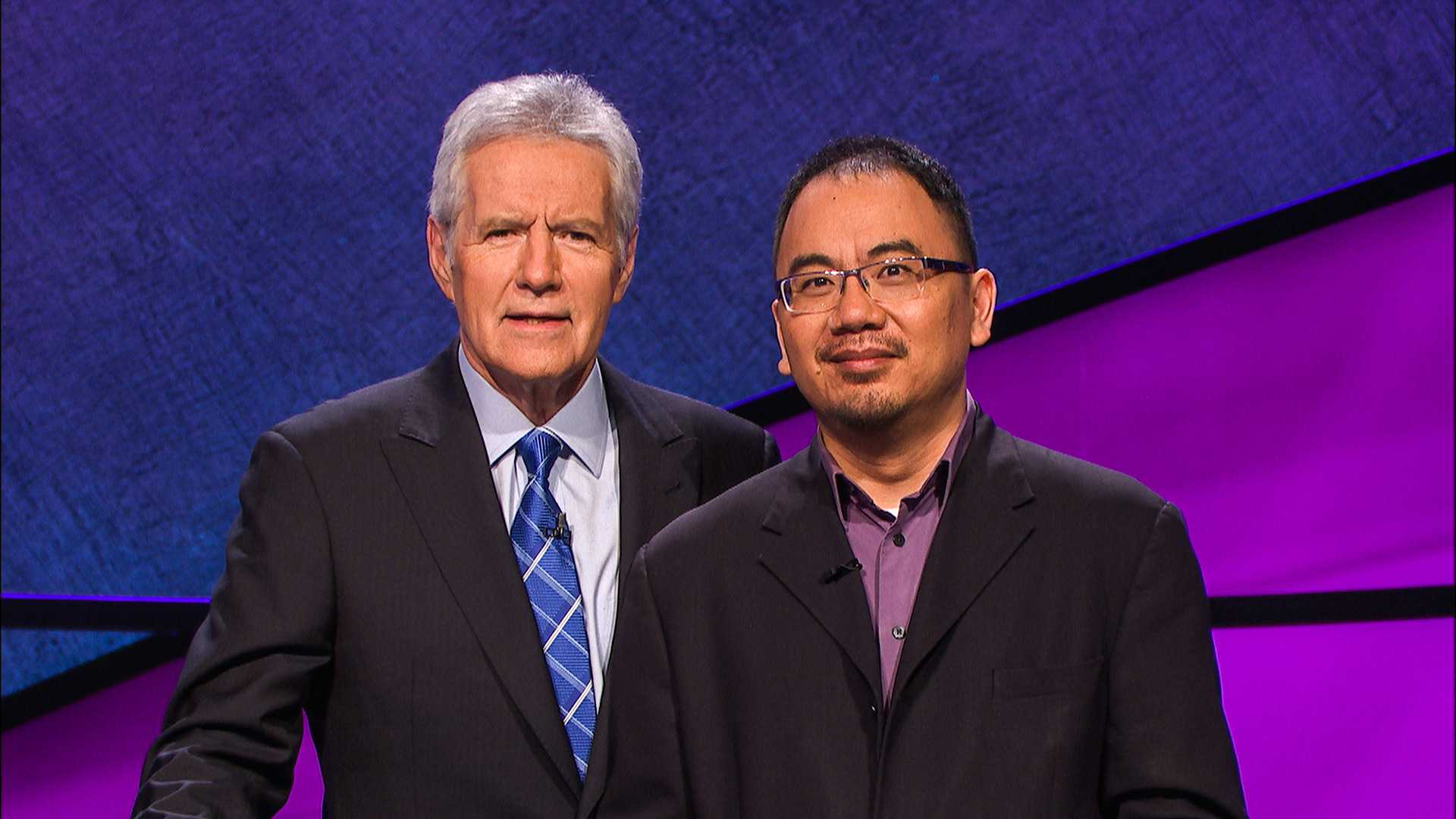 Assistant Professor of Music Theory Andrew Pau joins host Alex Trebek on the Jeopardy! set before one of Pau's six consecutive wins. He excelled in various topics, including Shakespeare and U.S. governors.