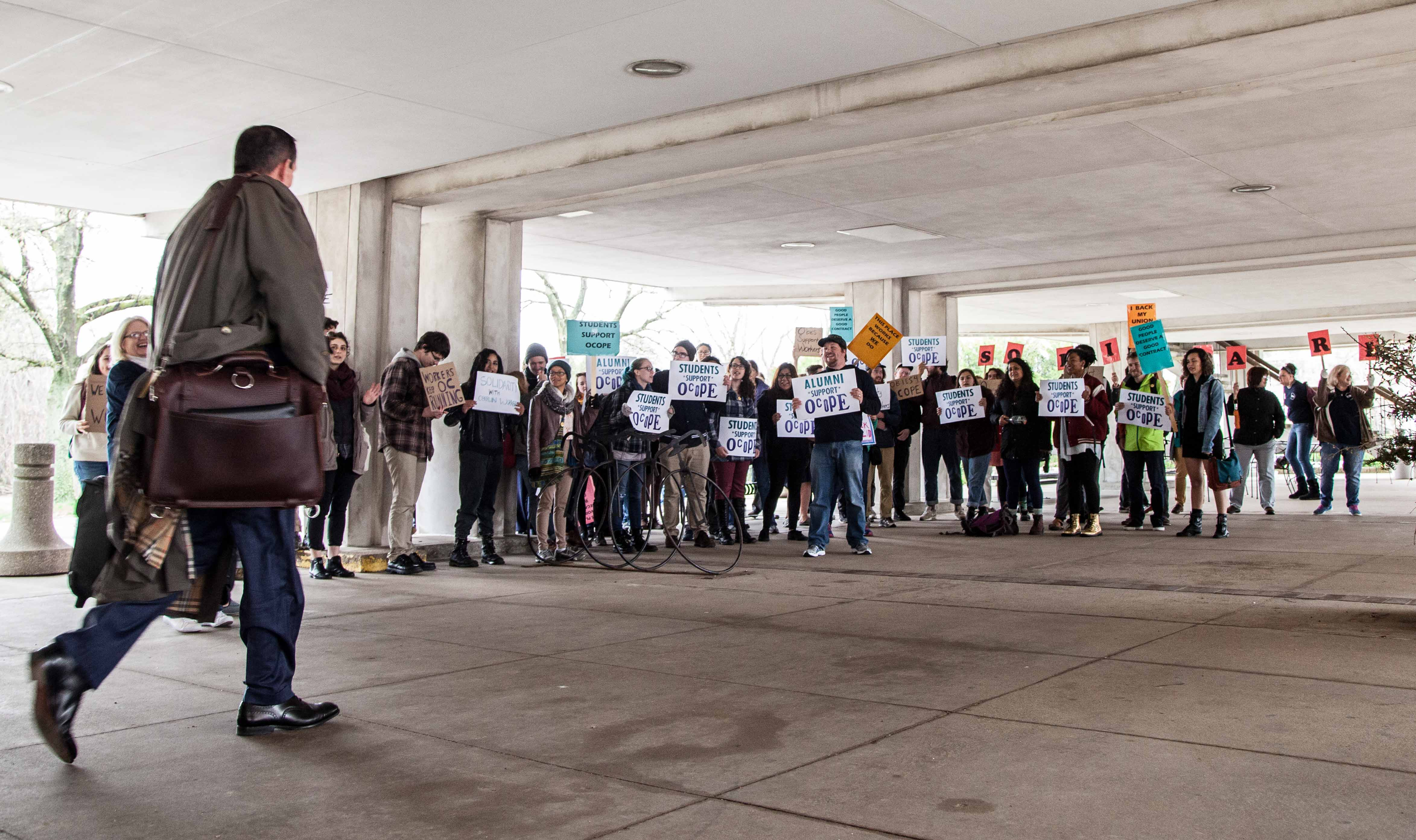 Michael J. Frantz, of Cleveland firm Frantz Ward LLP, leaves negotiations with OCOPE Friday afternoon as protestors line the exit route. The labor union, which represents 190 campus workers, is undergoing contract negotiations with administrators until June 30.