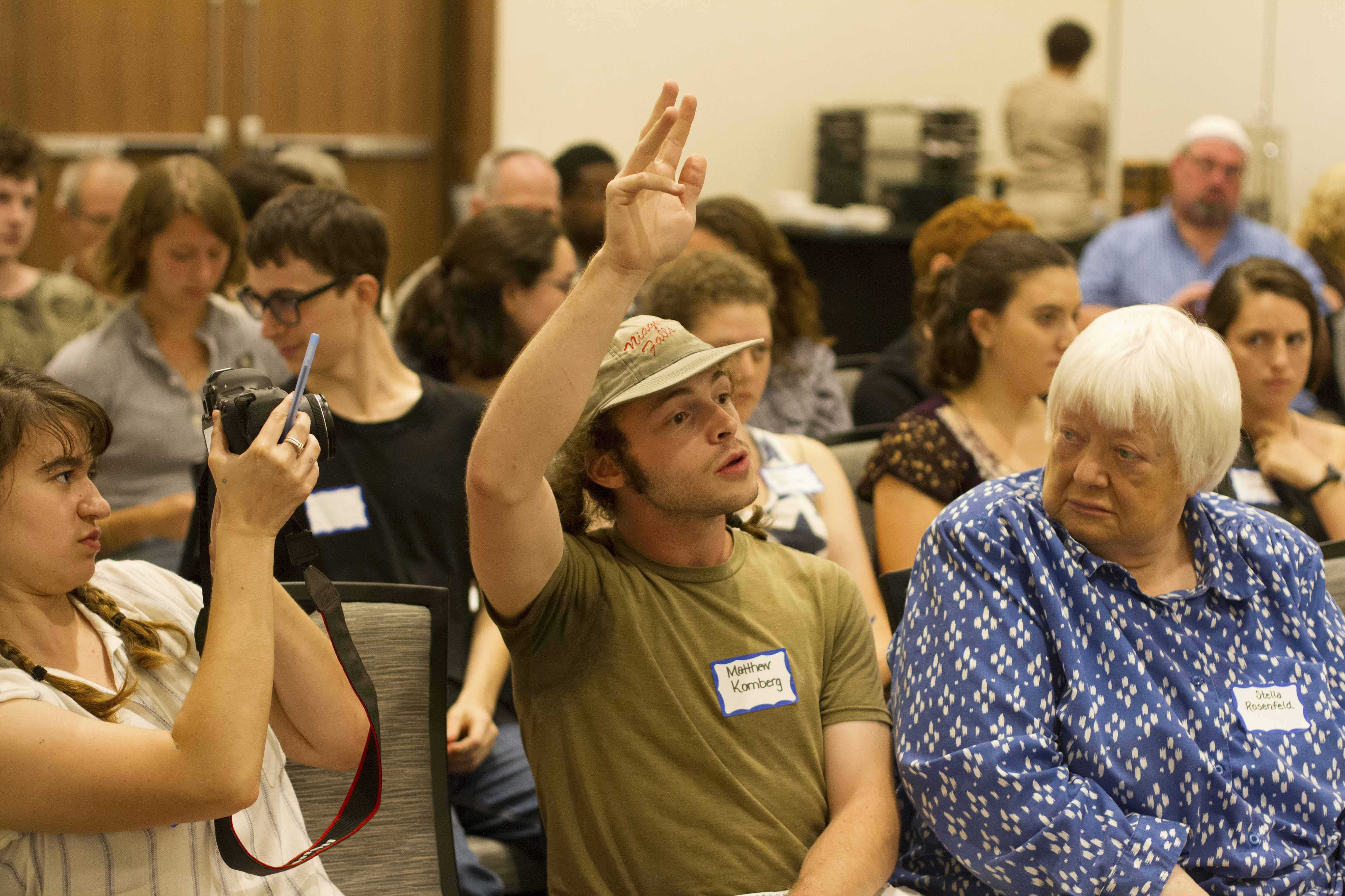 College junior Matthew Kornberg raises their hand at last night's Oberlin ACF anti-Semitism symposium at The Hotel at Oberlin. Student Senate released a letter condemning the group earlier in the week.