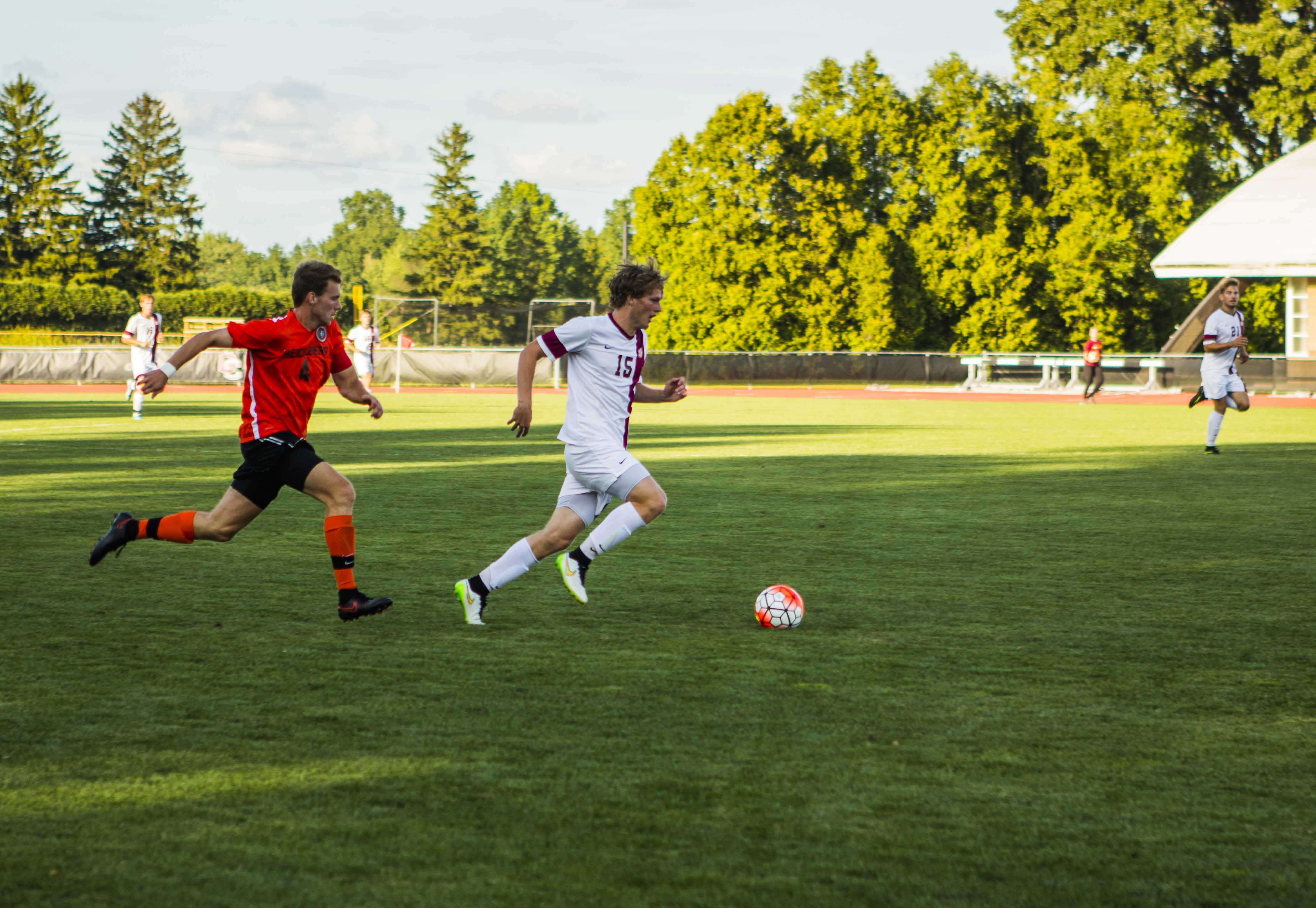 Junior forward Tim Williams dribbles away from a Heidelberg University defender. Oberlin defeated Heidelberg 3–1 in its season opener. The Yeomen now hold a 1–1 record.