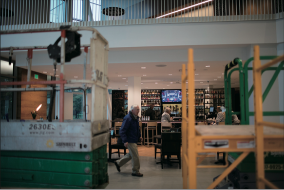 A visitor at The Hotel at Oberlin strolls past the bar. While construction continues on portions of the Peter B. Lewis Gateway Center, the hotel will host its first large conference Oct. 6–8 with participation from Arnold Schwarzenegger and famous environmentalist Bill McKibben.