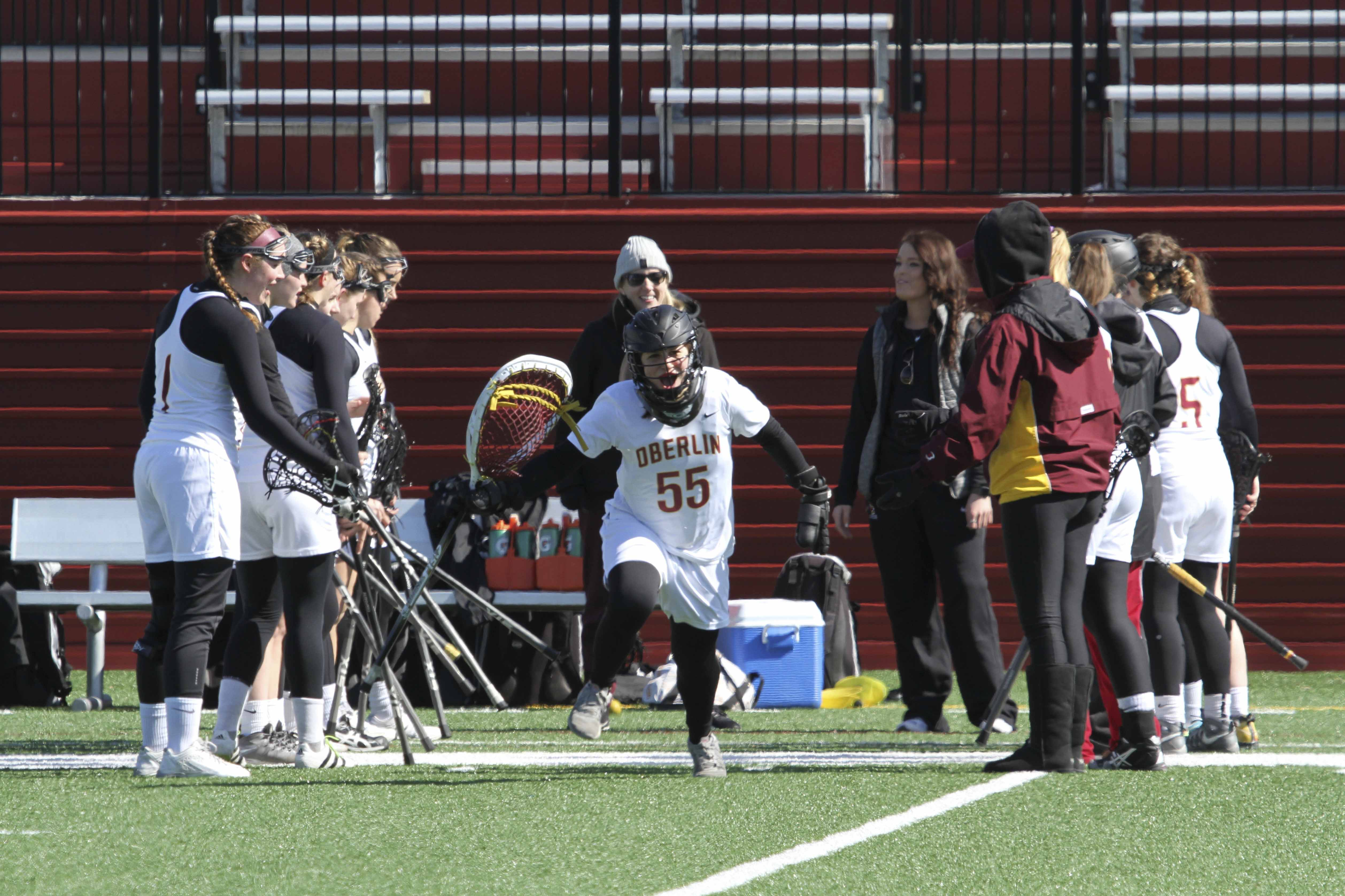 Sophomore goalie Siena Marcelle runs through a tunnel of teammates onto the field in Oberlin's home opener against Kalamazoo College March 4. The Yeowomen will continue conference play when they travel to take on Ohio Wesleyan University at 1 p.m. tomorrow.