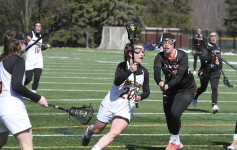 Junior Natalie Rauchle, named NCAC Player of the Week last week, maneuvers past a Kalamazoo College defender in Oberlin's 22–2 home-opening win over the Hornets. The Yeowomen are currently 3–0.