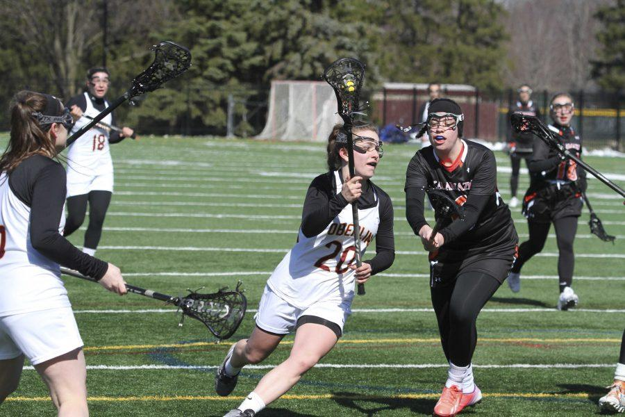 Junior Natalie Rauchle, named NCAC Player of the Week last week, maneuvers past a Kalamazoo College defender in Oberlins 22–2 home-opening win over the Hornets. The Yeowomen are currently 3–0.