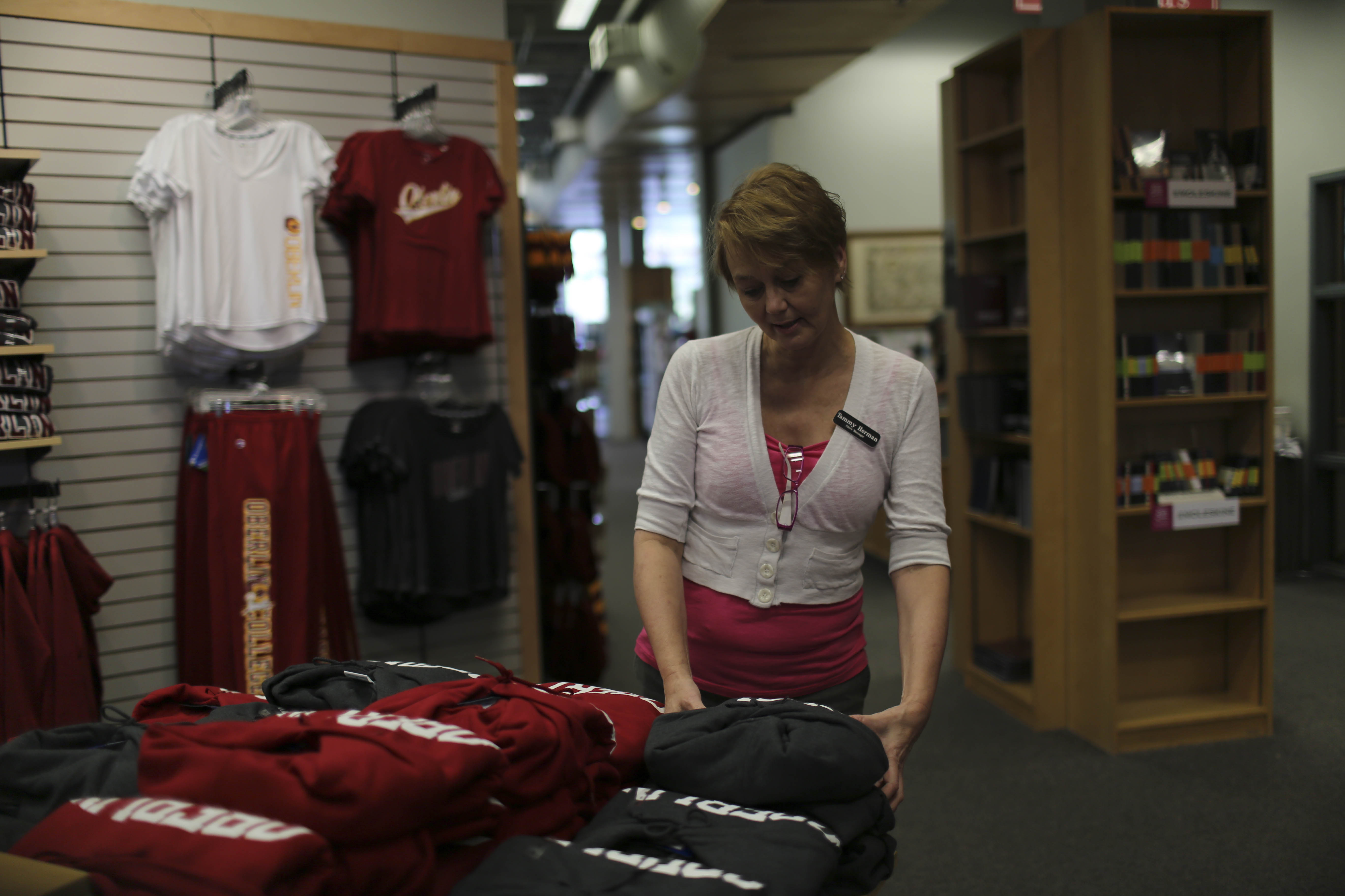College Bookstore Manager Tammy Herman reorganizes clothes Thursday. The College's Purchasing Committee will soon respond to the discovery that Nike breached the College's Sweatshop-Free Apparel Code of Purchasing.