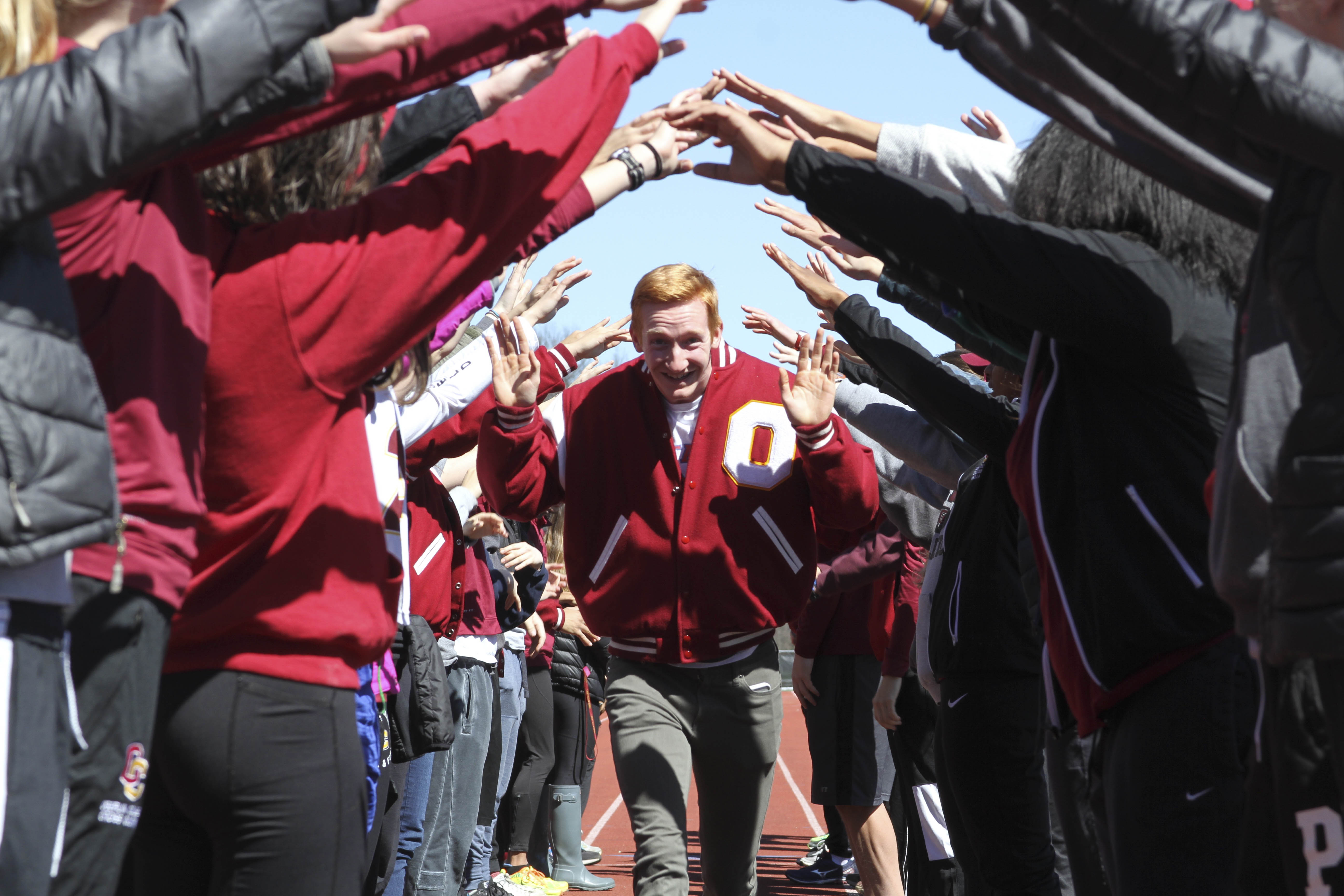 Senior Bradley Hamilton celebrates by running through a crowd of teammates at the Bob Kahn Invitational last Saturday. The event honored all senior members of the Yeomen and Yeowomen track and field teams.