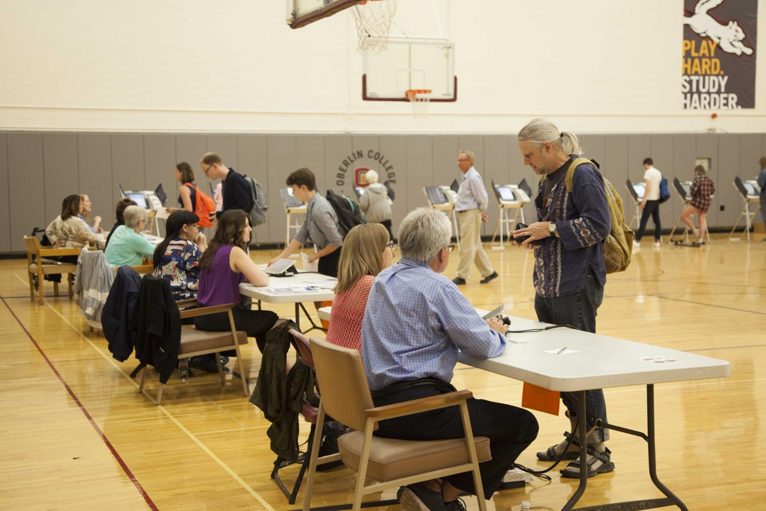 A community member picks up their ballot at Tuesday's primary election in Philips gym.