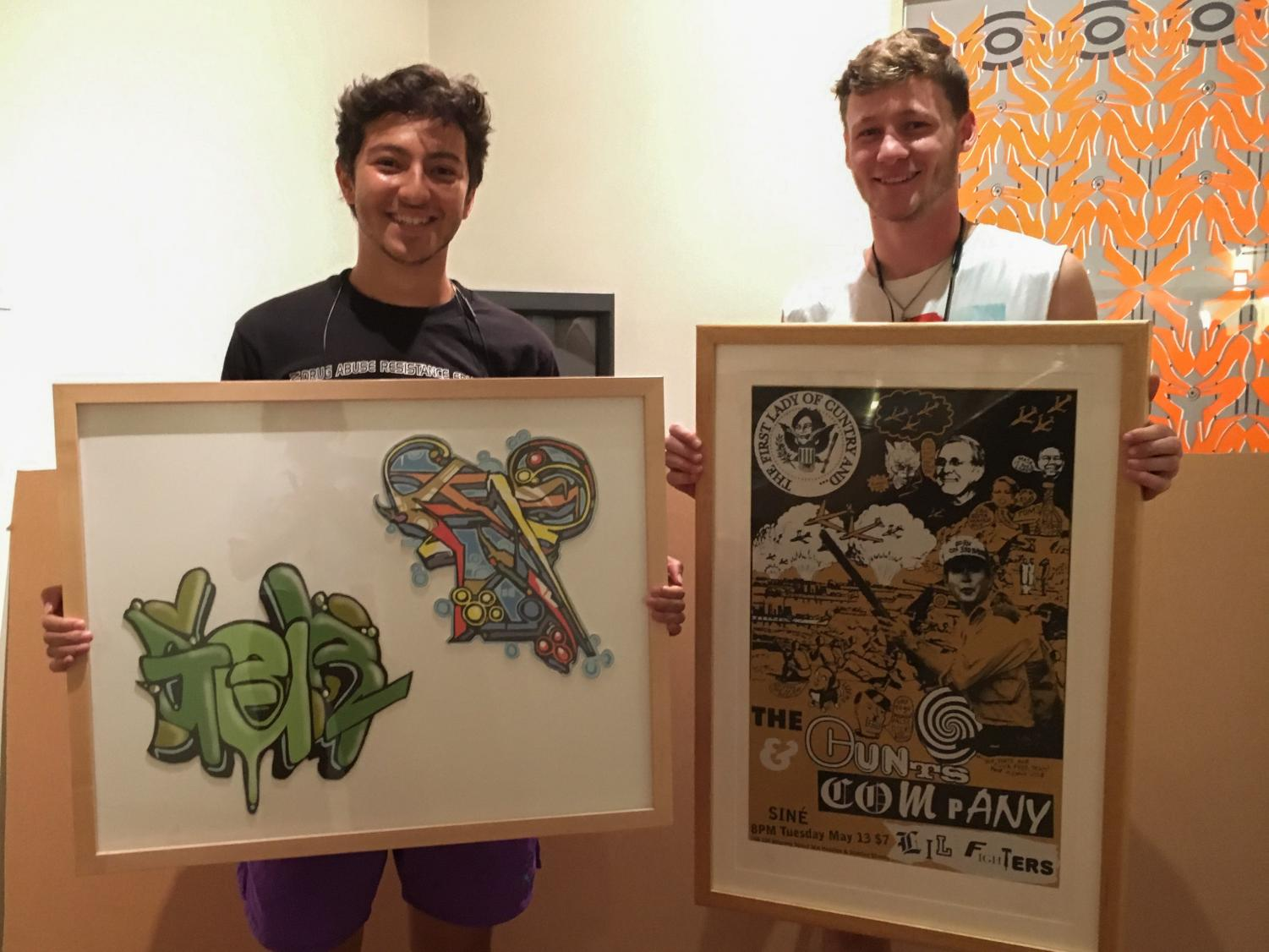 College seniors Brian James and Moses Riley hold their rented pieces, the last two available, from this year's Art Rental event. Students who participate in one of Oberlin's most noteworthy traditions can rent up to two pieces of art for the entire semester.