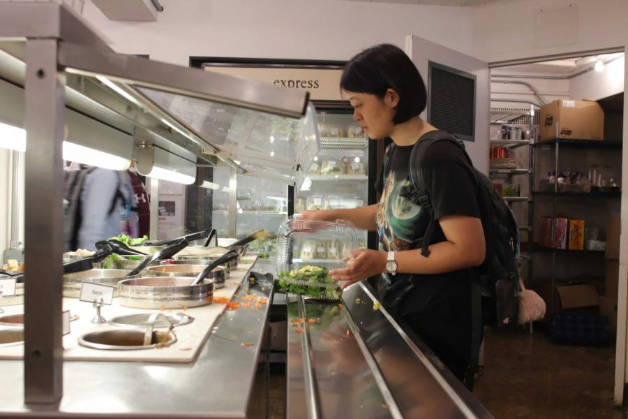 College Senior Andrea Wang grabs a salad at DeCafé's new salad bar, one of the many changes to this year's setup.