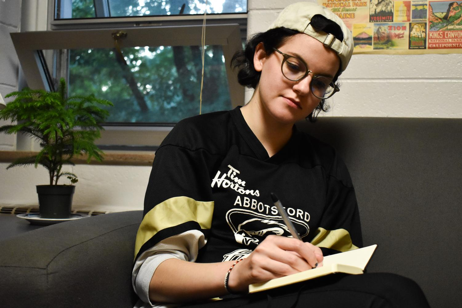 Conservatory senior Zoe Heuser writes in her diary. She is one of the many students who read their inner thoughts aloud during last Friday's Diary Reading Open Mic at the Cat in the Cream.