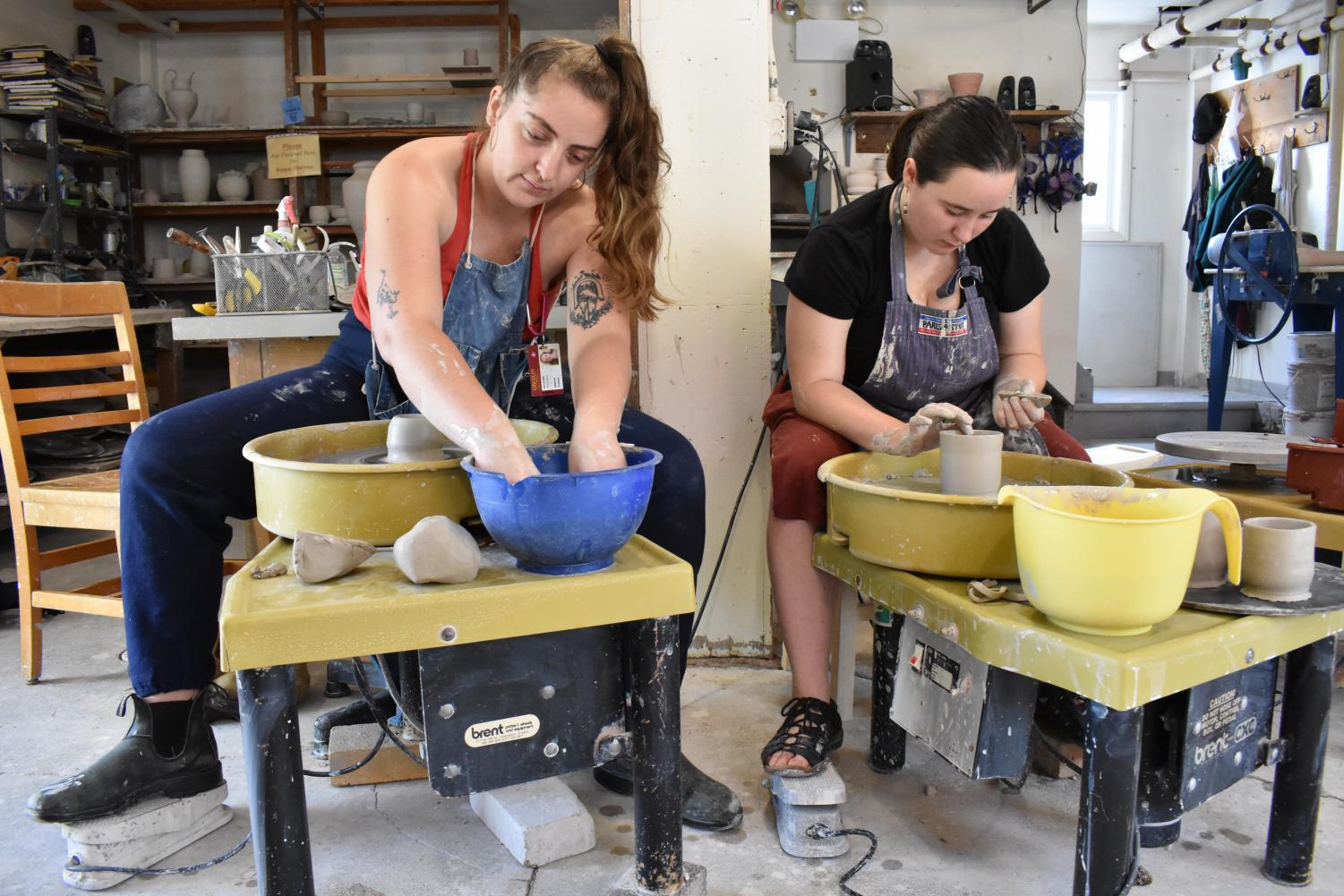 Members of the Pottery Co-Op sit at potters wheels. The co-op aims to be an inclusive space for students of all levels who want to learn how to create pottery.
