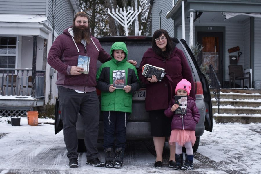 Rabbi Shlomo Elkan and wife Devorah Elkan standing in front of their home with two of their children holding books from the book drive.