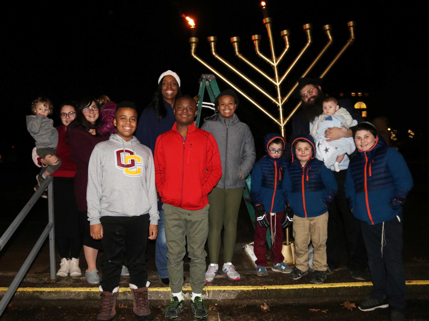 """Students and community members gathered in Wilder Bowl last Sunday night for the Grand Menorah Lighting Ceremony sponsored by Chabad at Oberlin. The event opened with remarks from President Carmen Ambar, followed by an a cappella performance by the Obertones. Rabbi Shlomo Elkan lit the menorah and led the crowd in three Hanukkah prayers. The event provided an opportunity for members of the Jewish community and others to celebrate the first night of Hanukkah.  """"As an Oberlin student, I'm often really busy with my classes and other commitments and I don't make practicing religion a priority,"""" College senior Juliet Flam-Ross said, """"but it was a really amazing feeling to be walking into the library to work on a paper and run into a Jewish practice that made me feel like I was home.""""  Attendees were encouraged to bring gently used books for Chabad's People of the Book project, an effort that donates books to people incarcerated in Lorain County."""