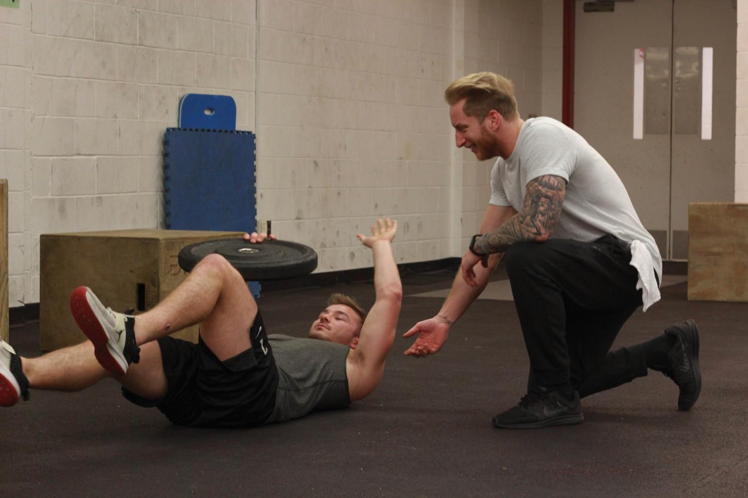 T3 athletic trainer Collin Taylor works out with College junior and football quarterback Zach Taylor.