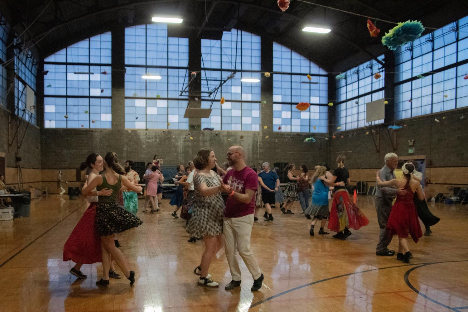 Oberlin's annual Dandelion Romp celebrated its 20th anniversary last weekend, filling Hales Gym with an animated crowd of dancers. Dandelion Romp is a three-day contra dance event where community members come together and practice the folk dance. Contra is an American dance form with Scottish, French, and English origins and features lines of couples who intermingle throughout a dance, led by a caller who teaches the dance's steps and rules.Oberlin hosted the event from 7:30 p.m. to 12 a.m. Friday, 9 a.m. to 12 a.m. Saturday, and from 9 a.m. to 4:00 p.m. Sunday, with supplemental workshops at the Cat in the Cream on Saturday and Sunday. The proceedings featured Dela Murphy and Alexandra Deis-Lauby, two touring callers, and touring bands Center Street and Sassafras Stomp. The event, which was organized by College seniors Mikaela Fishman and Caide Jackson, mid-year graduate Adam Work, College first-year Eliza Goodell, and double-degree senior Molly Tucker, drew a range of dancers — some Oberlin students but also many alumni, Oberlin residents, and contra dancers from various walks of life. Swing by next year or come to the on-campus contra dances each month if you'd like to join in the fun!