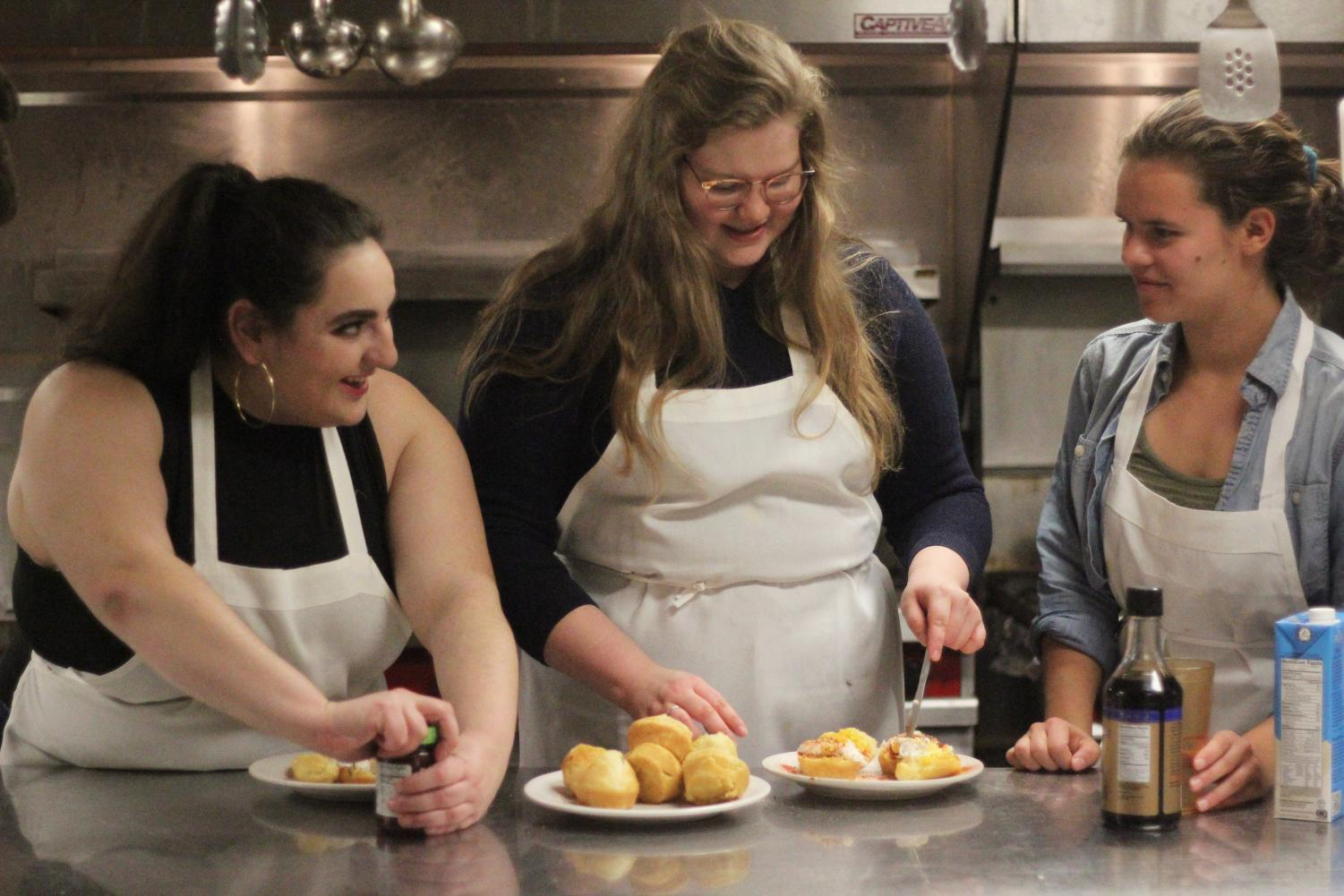 College junior Cat Robinson, College first-year Lily Lansdell, and College junior Katherine Carson baking late at night in the Pyle Co-op kitchen.