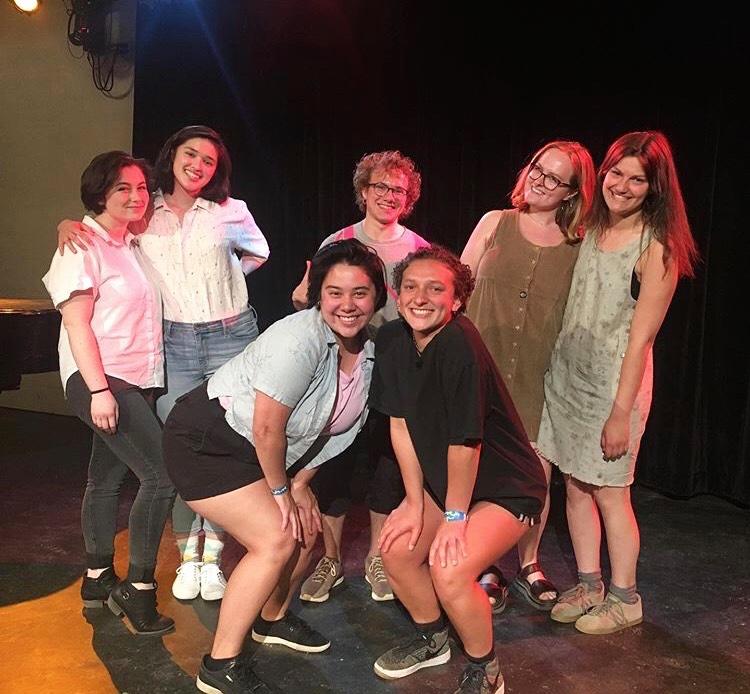 Senior Creative Writing students on stage at the Cat in the Cream after their reading. Back row: Rebecca Wood, Claire Wong, Jacob Fidoten, Madi Mettenburg, Gabi Shiner; Front row: Michelle Chu, Em Marcus.