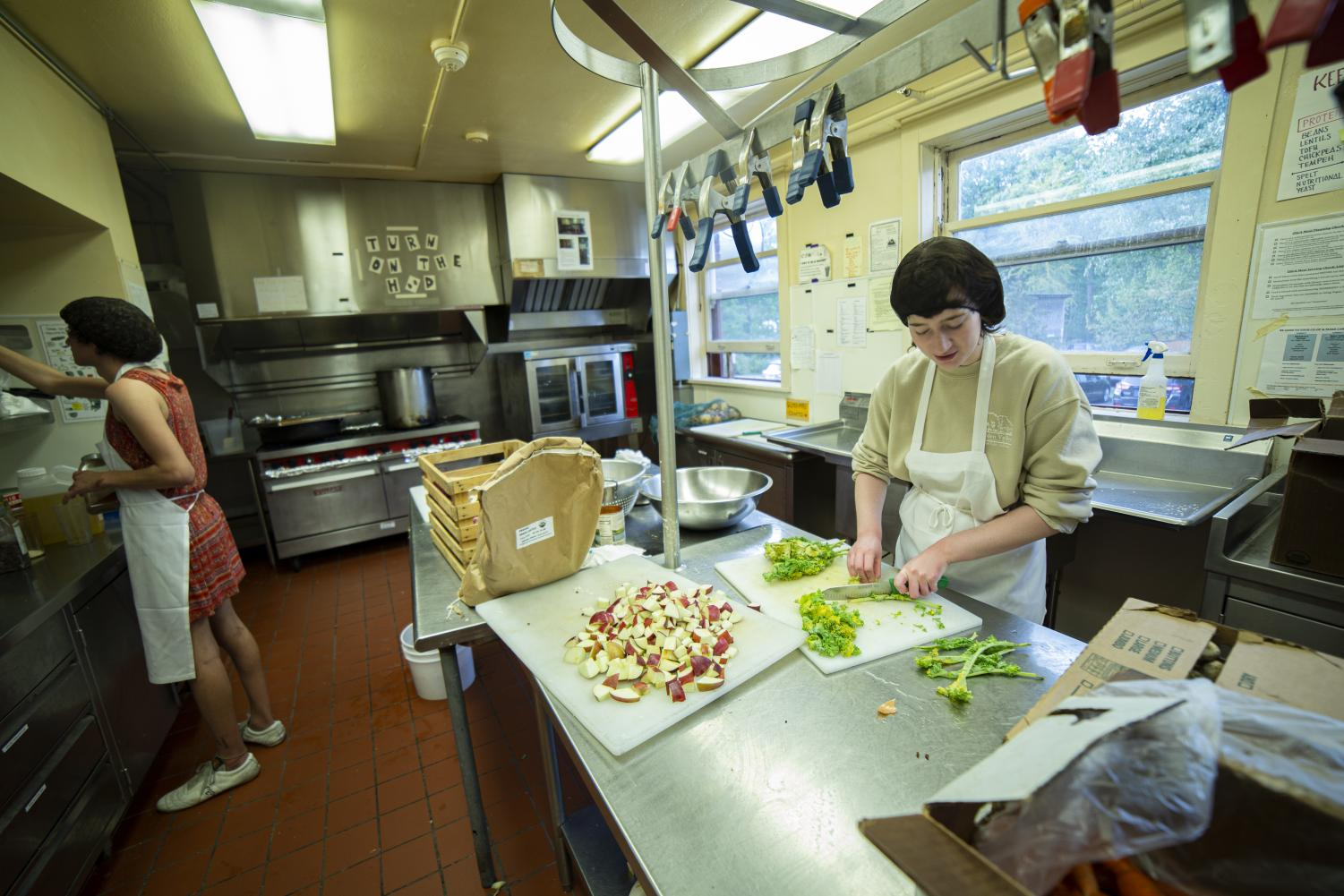 Members of the Oberlin Student Cooperative Association prepare a meal in the kitchen of Keep co-op. Canceled meals due to a turbulent interim period have raised concerns for OSCA members over ongoing negotiations with the College administration.