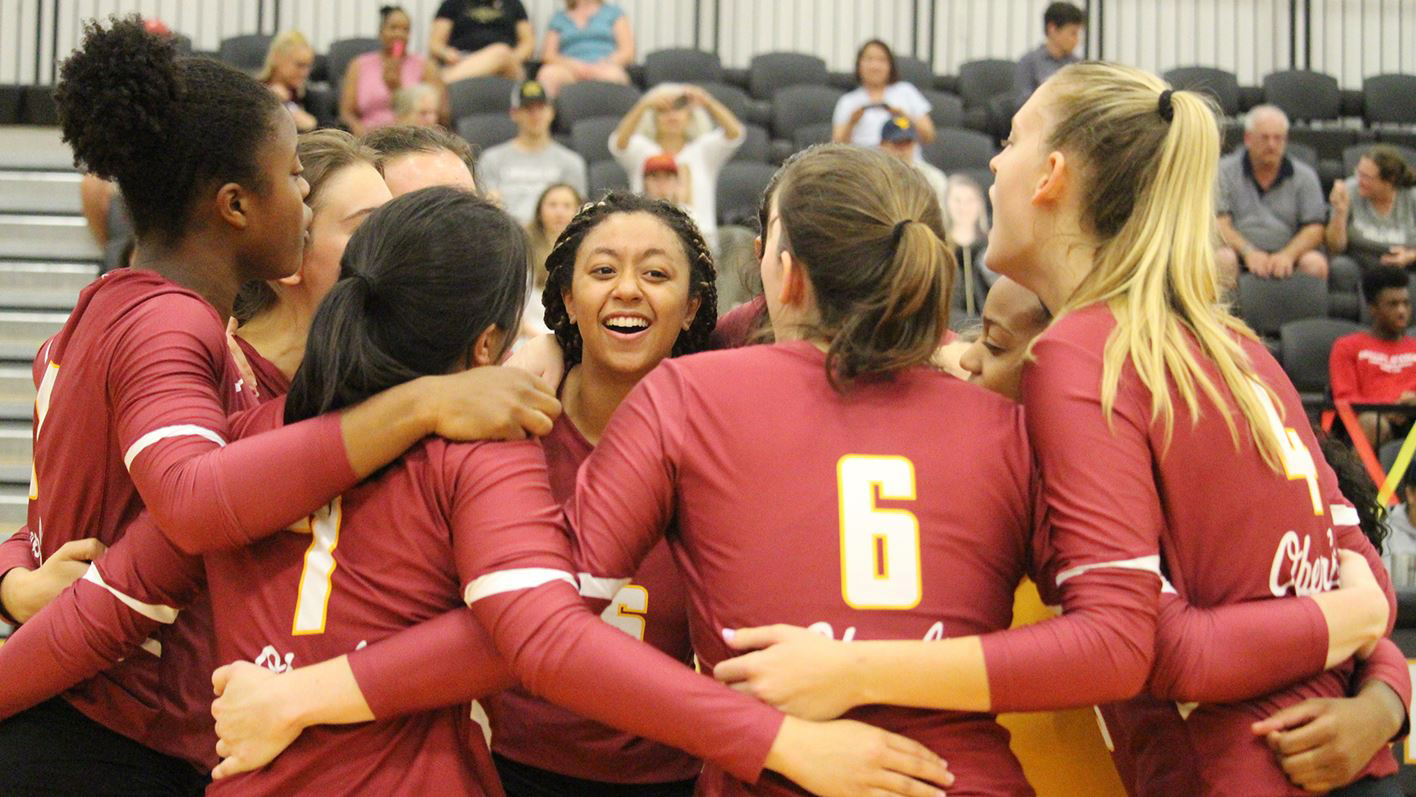 Oberlin women's volleyball players gather around College second-year Lauren Fitts.