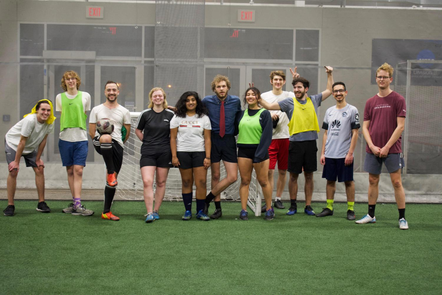 """On any given day, many of Oberlin's club sports teams that compete outside — such as club soccer, rugby, frisbee, and quidditch — can be found in North Fields.  However, North Fields becomes inaccessible with the arrival of Ohio's frigid winter months, when temperatures can drop below zero and snow and ice almost always covers the ground. To avoid the chill, club sports teams will often move their practices into Williams Field House. The space is also used by varsity sports teams, which take priority. As a result, some club sports frequently start practice as late as midnight — like the club soccer team pictured above.  """"Late night soccer is great because the energy is different from our regular [afternoon] practices,"""" said Laila Telles, College fourth-year and club soccer team captain. """"I think everyone feels more loose and comfortable and we all laugh even more than usual. [The fact] that we will play soccer at any time of day shows how dedicated we are."""""""