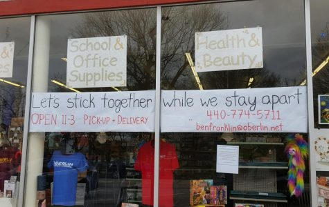 "Ben Franklin & Mindfair Books' window displays a banner to inform customers of their reduced hours and new delivery options in response to COVID-19. ""My message is, 'Let's stick together while we stay apart,'"" said Ben Franklin's owner Krista Long. ""I think everyone, all the business owners in Oberlin, … have that also at their heart."""