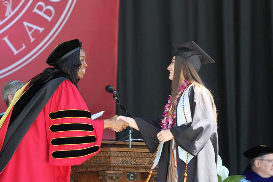 President Carmen Twillie Ambar shakes a graduate's hand at Oberlin's 2019 commencement ceremony.