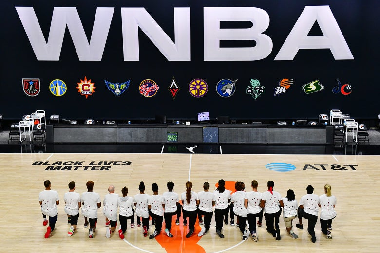 WNBA's Washington Mystics kneeling and wearing T-shirts printed with seven bullet holes to protest the police shooting of Jacob Blake.  Courtesy of Slate.com.