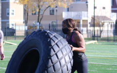 Oberlin College President Carmen Twillie Ambar flipping a tire.
