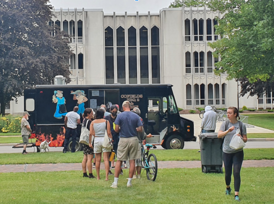 Community members and students gather around the Cofield's food truck.