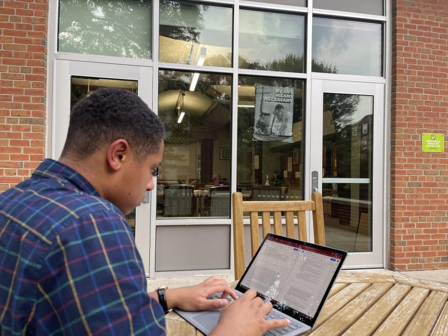 Photo by Diwe Augustin-Glave. College second-year Donnie Harris sits on Bailey House porch doing homework.